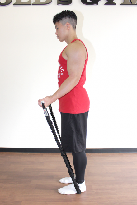 1.軽く顎を引き、腰幅に足を開いて真っ直ぐに立つ。両足で押さえてチューブの長さを調節し、腰の位置でチューブの端を持つ。