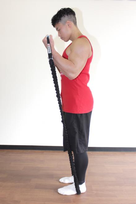 2.肘を曲げて肩の高さまでチューブを引き伸ばす。1〜2を繰り返す。