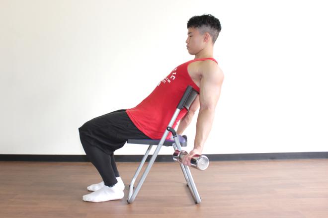 1.椅子に浅く腰掛け、背もたれに寄りかかる。足は腰幅程度に開く。手首を外側にまわして両手にダンベルを持つ。
