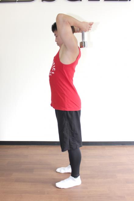 1.足を肩幅に開いて真っ直ぐに立ち、顎を軽く引いて正面を見る。両手の親指と人差し指の間でダンベルを支え、頭の後ろで持つ。