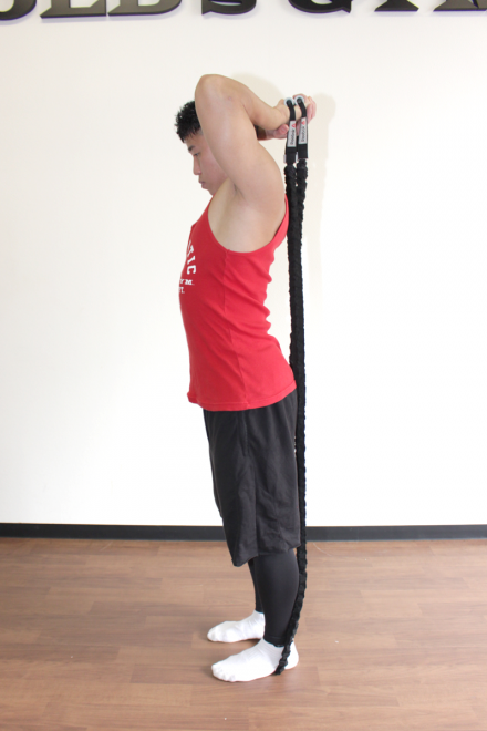 1. 足を肩幅に開いて真っ直ぐに立ち、顎を軽く引いて正面を見る。両足でチューブを押さえて長さを調節し、頭の後ろでチューブの端を持つ。