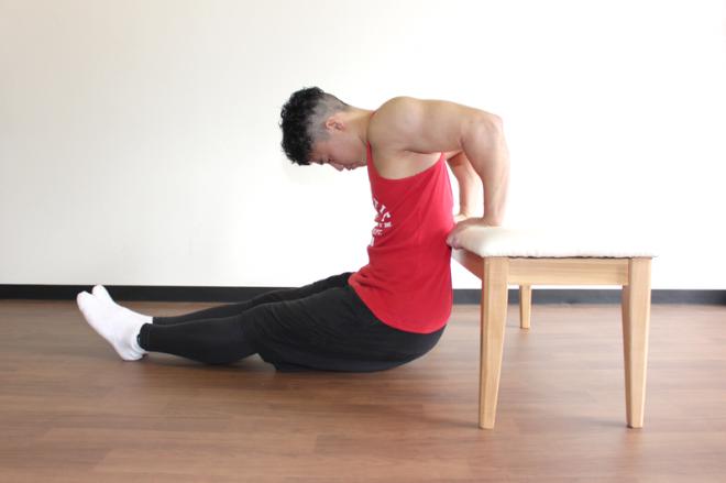2.肘を90度曲げて体を深く落とす。お尻が床面につかないように腕の力で体をしっかりと支える。1〜2を繰り返す。