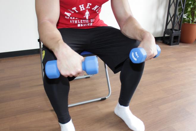 1.足を肩幅に開いて椅子に深く腰掛け、腕を腿にのせて固定し前かがみになる。手のひらを下に向けてダンベルを握る。