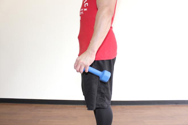 1.足を軽く開いてまっすぐに立ち、軽く顎を引く。両手それぞれでダンベルの前端を持つ。