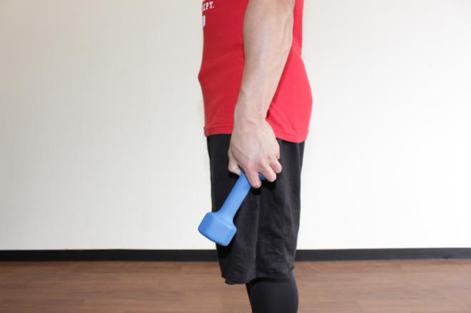 1.足を軽く開いてまっすぐに立ち、軽く顎を引く。両手それぞれでダンベルの後端を持つ。