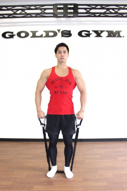 チューブを使ったサイドレイズ [1]脚を肩幅に、つま先を軽く開いて真っ直ぐに立つ。足でチューブを押さえたまま、端を両手で持つ。