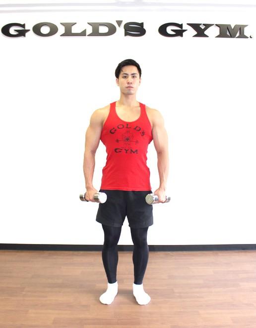 ダンベルを使ったサイドレイズ [1] 脚を肩幅に、つま先を軽く開いて真っ直ぐに立ち、ダンベルを両手で持つ。