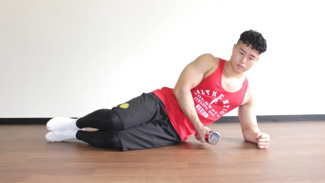 1.床に横向きになり、膝を少し曲げて足を揃える。床に下側の腕の肘をつき、肘に体重をかける。上側の手でダンベルを持つ。