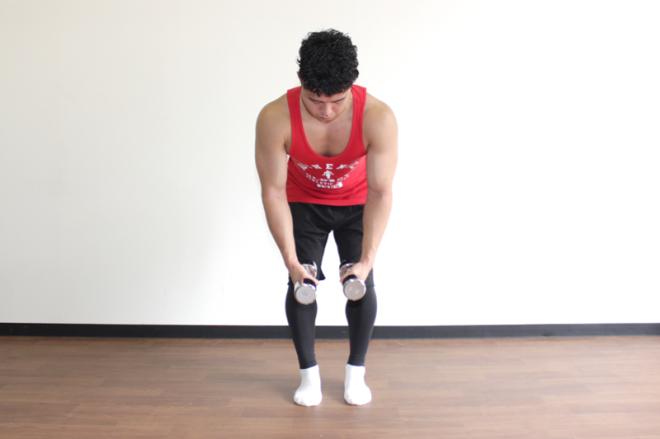 1.足は腰幅に、膝を軽く曲げて前傾姿勢になる。手のひらが向かい合うように両手にそれぞれダンベルを持つ。
