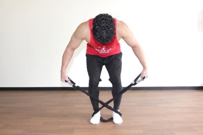 1.足は腰幅に、膝を軽く曲げて前傾姿勢になる。チューブを両足で押さえてX字になるように固定し、ピンと張って負荷を乗せておく。