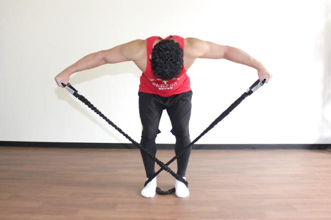 2.体は前傾したままで、羽ばたくように腕を上げ、チューブを引き伸ばす。1〜2を繰り返す。