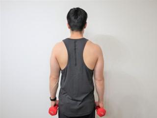 背筋を鍛える際の僧帽筋を鍛えるダンベルシュラッグの動作 1.両手にダンベルを持ち直立する。(背面)