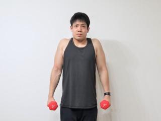 背筋を鍛える際の僧帽筋を鍛えるダンベルシュラッグの動作 2.首をすくめるように肩を上にあげる。(正面)1→2を繰り返す。