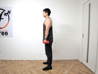 背筋を鍛える際の脊柱起立筋を鍛えるダンベルデッドリフトの動作 1.両手にダンベルを持ち、肩幅ぐらいの位置に足を広げて直立する。(側面)