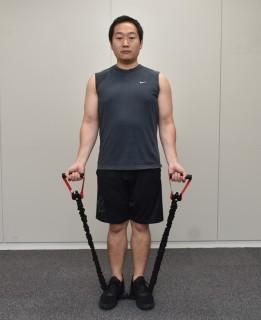 1.両手でトレーニングチューブを握って、手のひらを前に向ける。2.トレーニングチューブを踏み、まっすぐ立つ。