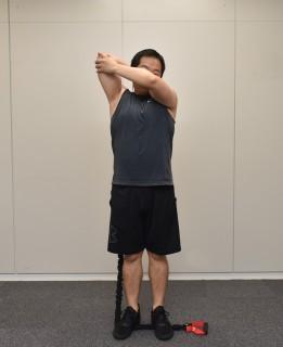 1.片手でトレーニングチューブを握って、肘を上にあげて、手を頭の後ろに。2.トレーニングチューブを踏み、まっすぐ立つ。