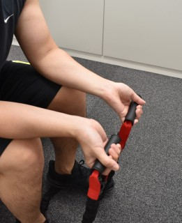 2.両手でトレーニングチューブを握って、手のひらを上に向けて、膝に手首を置く。