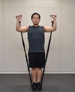 1.両手でトレーニングチューブを握って、まっすぐ立つ。2.トレーニングチューブを踏む。3.手を肩の高さに、肩幅より少し広く構える。