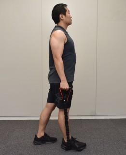 1.両手でトレーニングチューブを握って、まっすぐ立つ。2.トレーニングチューブをトレーニングする側の脚で踏む。