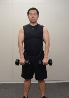 1.ダンベルを身体の前で両手に持って真っ直ぐ立ち、ダンベルを肘から上に上げる。(肩から上がらないように)
