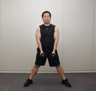 1.両手にそれぞれダンベルを持ち 脚を肩幅より1足分外に広げて立ち、つま先を斜め45度に向ける。