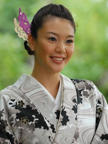 モノクロの柄のある着物に白と紫のヘアアクセサリーを合わせる知花くらら