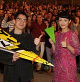 来場者と一緒に折り紙で作った紙飛行機を手に
