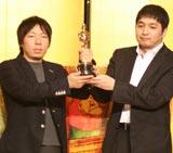 誇らしげにトロフィーを掲げる加藤監督(左)と日下部雅謹プロデューサー