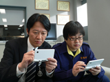 新CMでゲームに熱中する(左から)捜査一課・伊丹慶一(川原和久)と鑑識課・米沢守(六角精児)