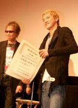 三池崇史監督(左)から卒業証書を手渡された小栗旬 【映画『クローズ ZERO II』初日舞台あいさつにて】