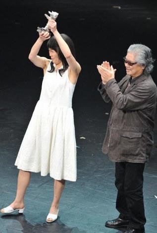 銀熊賞のトロフィーを高く掲げる寺島しのぶ(右は若松孝二監督)