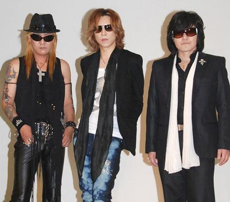 イベントで壁の前に立っているメンバー三人のX JAPANの画像