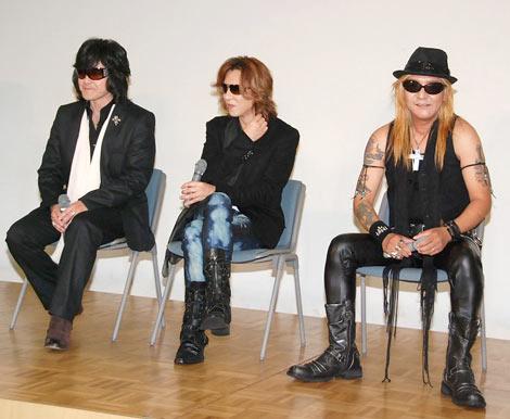 イベントで椅子に座ってインタビューを受けているX JAPANの画像