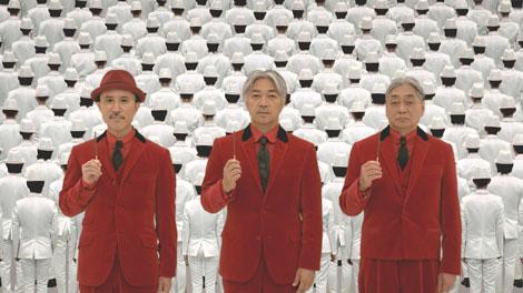 真っ白なスーツ姿の群衆に囲まれるYMO(左から)高橋幸宏、坂本龍一、細野晴臣