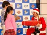 """セガトイズ『笑顔フォトコンテスト』の会見で、子どもたちにプレゼントを贈る""""サンタ""""渡部陽一 (C)ORICON DD inc."""
