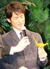 映画『太平洋の奇跡 フォックスと呼ばれた男』の舞台あいさつで折り鶴を手に持ち微笑む竹野内豊