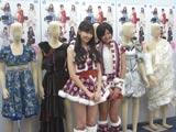 新宿駅で展示する衣装を前に笑顔を見せる小嶋陽菜と宮澤佐江(右)