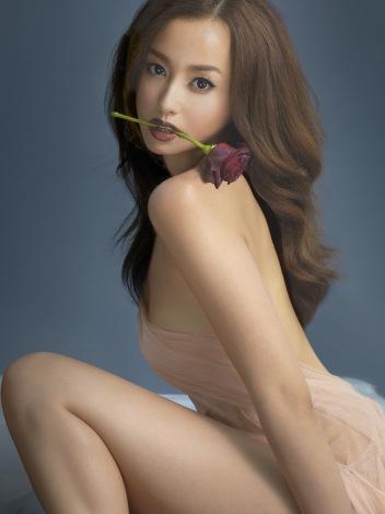 ベージュのドレスを着てバラを咥えている沢尻エリカの画像