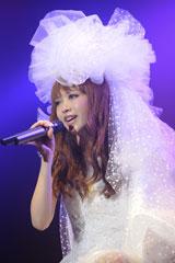 ウエディングドレス風の衣装で歌うYU-A