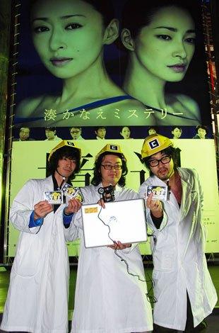ホンモノ『境遇』看板の前でニセモノティッシュを手にするAR三兄弟
