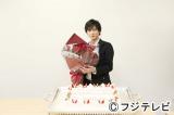 「中村俊介 祝 浅見光彦シリーズ30作 10th Anniversary from2003」とデコレーションされたケーキと30本の赤いバラの祝福に笑顔で答える中村俊介