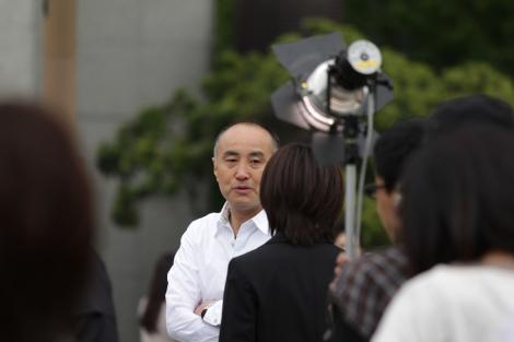 NHK連続テレビ小説『純と愛』がクランクイン 撮影の合間に夏菜(手前のスーツ姿)に声をかける作者の遊川和彦氏