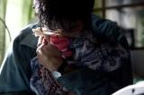 他界した妻が、片づけ忘れた洗濯物に顔をうずめる主人公 (C)2012「その夜の侍」製作委員会