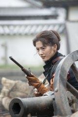 第1話冒頭でスペンサー銃を手に男さながらに戦う八重を演じる綾瀬はるか(C)NHK