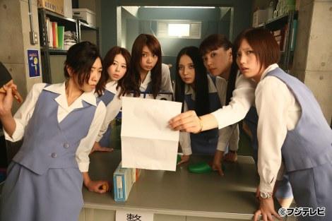 ショムニの制服で何かを照らし合わせて確認する堀内敬子