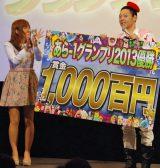 優勝賞金を代わりに受け取る司会のライト東野(右)