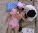 ベビーシッターとなり赤ちゃんに扮した斉藤氏のお守りをするライセンス藤原(C)NTV