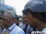 タイ・バンコクで取材をする榎並大二郎アナウンサー。左の白髪の男性は反政府デモ隊のリーダーのステープ元副首相