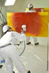 腕があっても塗装が難しいというレッド。職人さんたちはいろんな角度から確認しながらも、躊躇なく色を重ねていきます(=広島・マツダ本社) (C)oricon ME