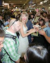 空港に集まったファンに笑顔を見せるテイラー・スウィフト